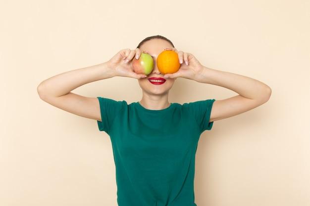 Vista frontal mujer joven en camisa verde oscuro y jeans con manzana y naranja sobre beige