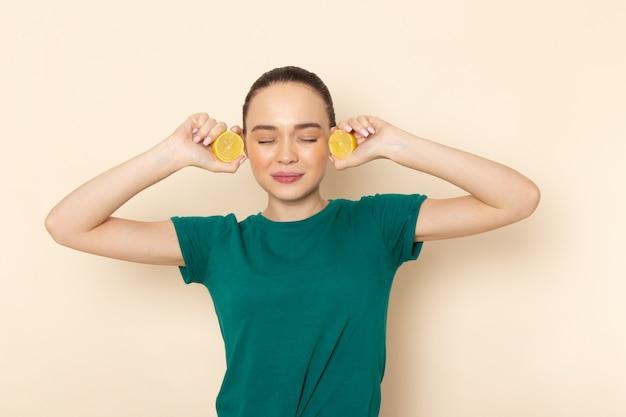 Vista frontal mujer joven en camisa verde oscuro y jeans con rodajas de limón en beige
