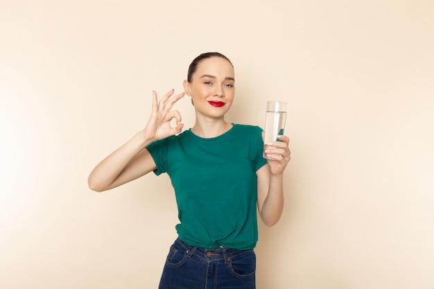 Vista frontal mujer joven en camisa verde oscuro y jeans sosteniendo un vaso de agua sonriendo en beige
