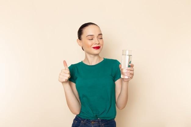 Vista frontal mujer joven en camisa verde oscuro y jeans con vaso de agua en beige