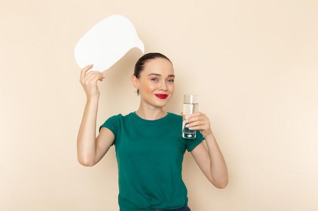 Vista frontal mujer joven en camisa verde oscuro y jeans con vaso de agua y cartel blanco en beige
