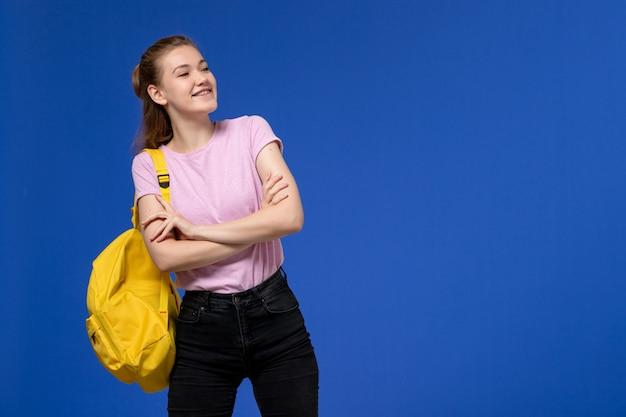 Vista frontal de la mujer joven en camiseta rosa con mochila amarilla posando y riendo en la pared azul