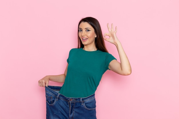 Vista frontal mujer joven en camiseta verde mostrando su cuerpo delgado en la pared rosa cintura deporte ejercicio entrenamiento belleza atleta delgado