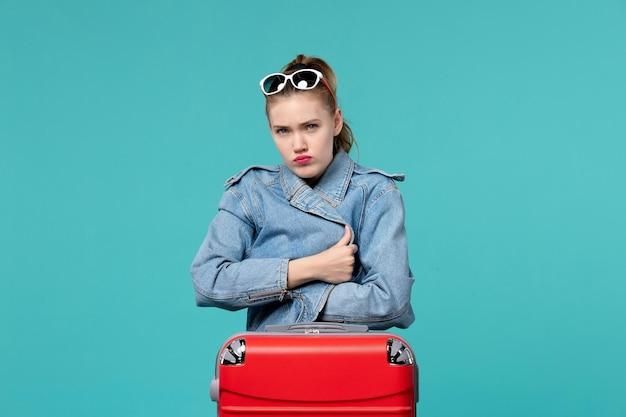 Vista frontal mujer joven en chaqueta azul preparándose para el viaje posando en el espacio azul