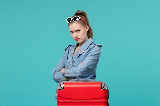 Vista frontal mujer joven en chaqueta azul preparándose para el viaje y sintiéndose enojada en el espacio azul