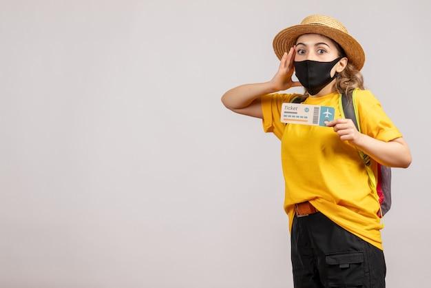 Vista frontal de la mujer joven confundida con máscara negra con boleto de viaje en la pared blanca