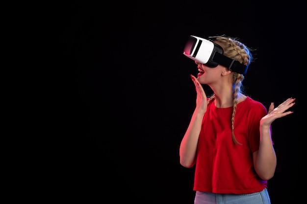Vista frontal de la mujer joven emocionada jugando vr sobre superficie negra