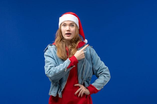 Vista frontal mujer joven con expresión emocionada sobre fondo azul vacaciones de año nuevo navidad