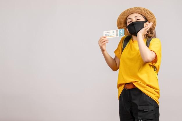 Vista frontal de la mujer joven feliz con mochila con máscara negra con boleto de viaje en la pared blanca