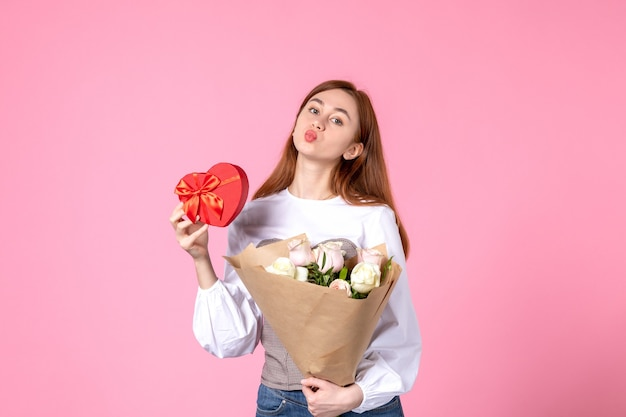 Vista frontal mujer joven con flores y presente como regalo del día de la mujer sobre fondo rosa marzo horizontal igualdad amor sensual mujer fecha femenina