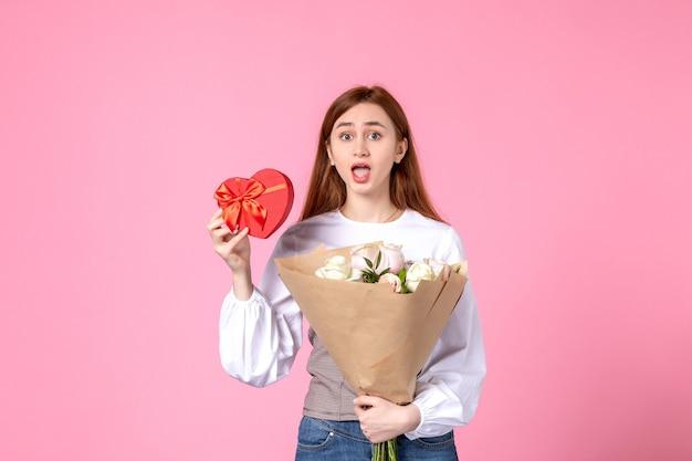 Vista frontal mujer joven con flores y presente como regalo del día de la mujer sobre fondo rosa marzo horizontal mujer fecha igualdad amor sensual femenino