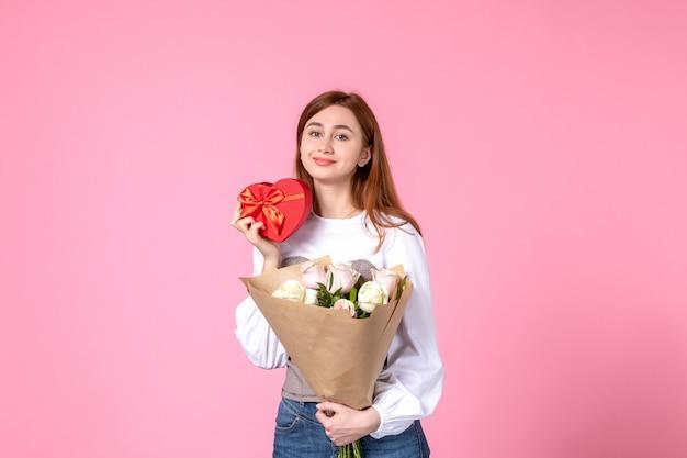 Vista frontal mujer joven con flores y presente como regalo del día de la mujer sobre fondo rosa rosa marzo horizontal fecha femenina mujer amor sensual igualdad
