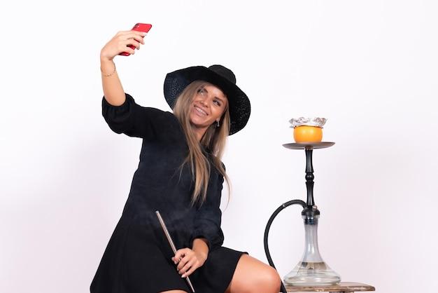Vista frontal de la mujer joven fumando narguile y tomando selfie en pared blanca
