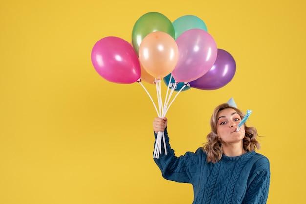 Vista frontal mujer joven con globos de colores