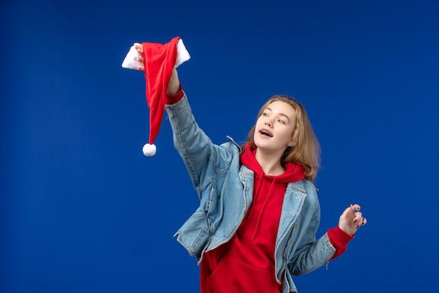 Vista frontal mujer joven con gorra roja sobre fondo azul vacaciones navidad color año nuevo