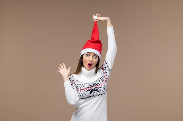 Vista frontal mujer joven con gorro rojo de navidad sobre fondo marrón emoción de vacaciones de navidad