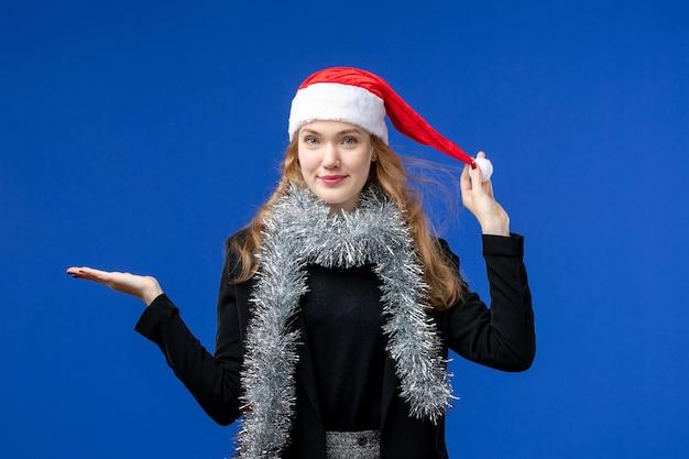 Vista frontal de la mujer joven con guirnaldas de año nuevo en la pared azul