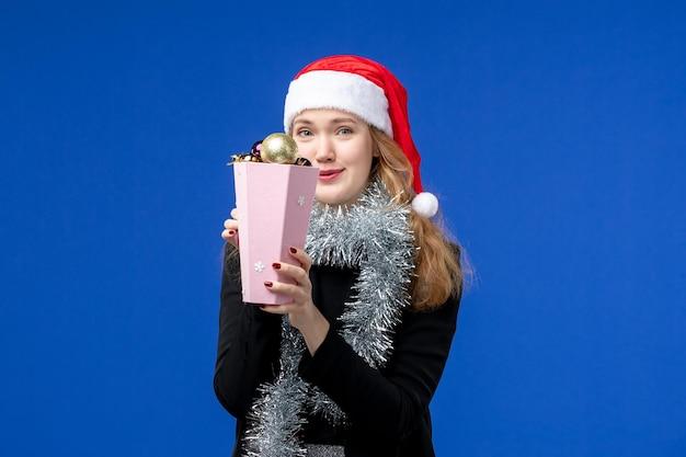 Vista frontal de la mujer joven con juguetes de árbol de año nuevo en la pared azul
