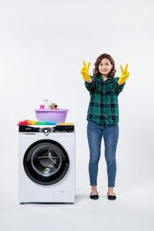 Vista frontal de la mujer joven con lavadora en guantes amarillos en la pared blanca