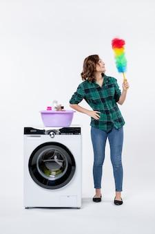 Vista frontal de la mujer joven con lavadora con limpiador de polvo en la pared blanca