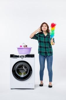 Vista frontal de la mujer joven con lavadora en la pared blanca