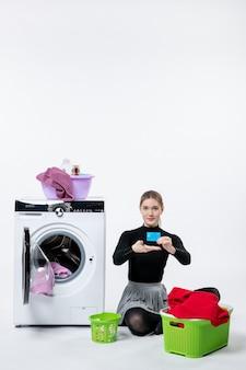 Vista frontal de la mujer joven con lavadora con tarjeta bancaria en la pared blanca