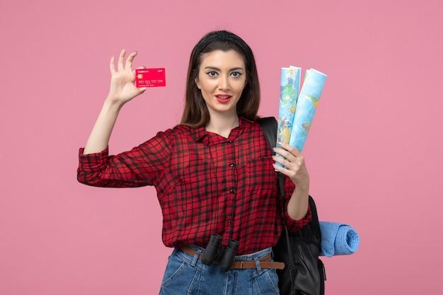 Vista frontal mujer joven con mapas y tarjeta bancaria en el color de fondo rosa mujer humana