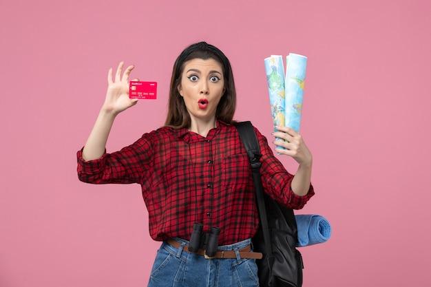 Vista frontal mujer joven con mapas y tarjeta bancaria en el color humano de la mujer de fondo rosa