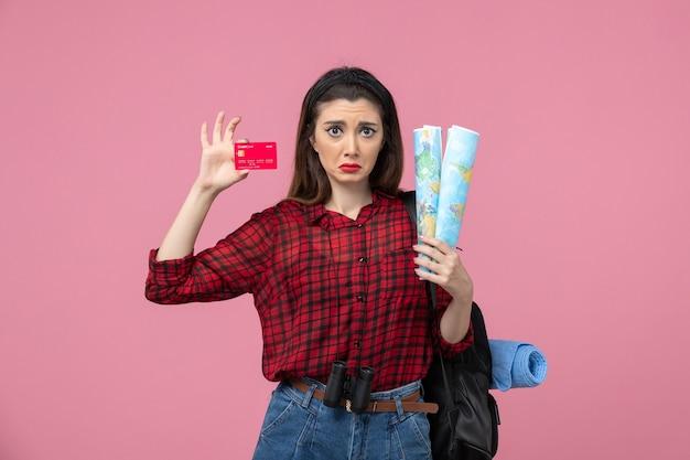 Vista frontal mujer joven con mapas y tarjeta bancaria sobre fondo rosa claro color mujer humana
