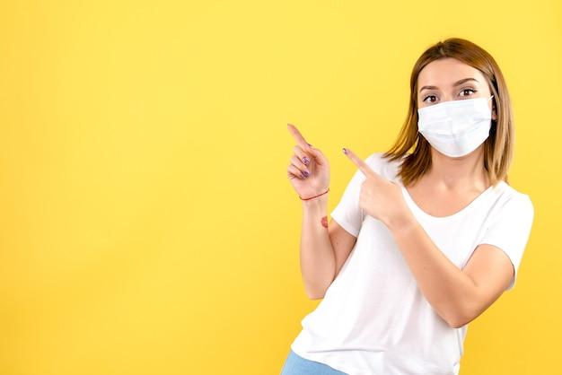 Vista frontal de la mujer joven en máscara estéril en pared amarilla
