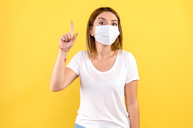 Vista frontal de la mujer joven en máscara en la pared amarilla