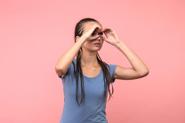 Vista frontal de la mujer joven mirando a través de los dedos en rosa