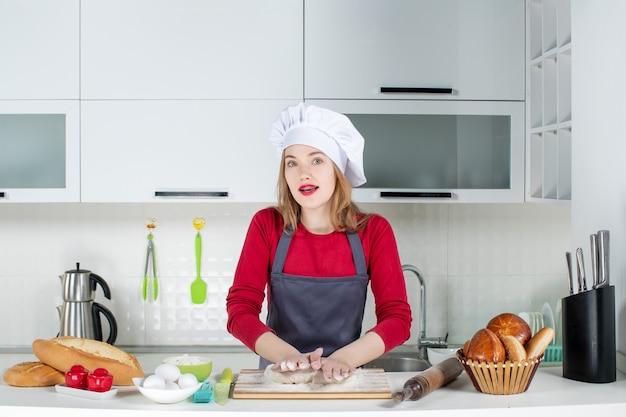 Vista frontal mujer joven ocupada en sombrero de cocinero y delantal amasando masa en la cocina