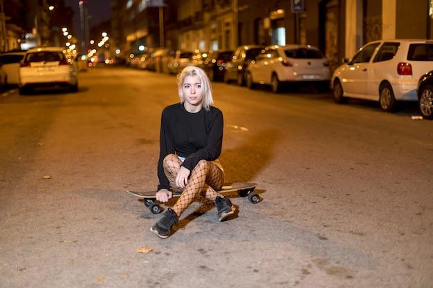 Vista frontal de una mujer joven en pantalones cortos en una tabla larga mientras mira la cámara por la noche en la ciudad