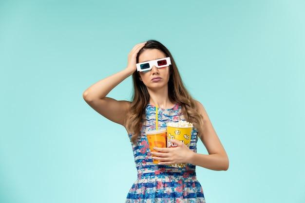 Vista frontal mujer joven con paquete de palomitas de maíz y bebida en gafas de sol d sobre superficie azul