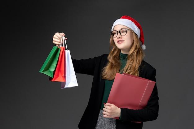 Vista frontal mujer joven con paquetes en la pared oscura regalo año nuevo navidad