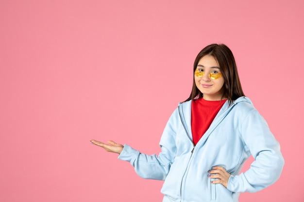 Vista frontal de la mujer joven con parches en los ojos debajo de los ojos en la pared rosa