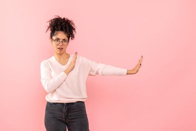 Vista frontal de la mujer joven en la pared rosa