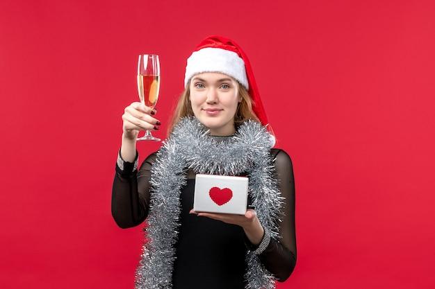 Vista frontal mujer joven con presente celebrando en la pared roja color vacaciones navidad