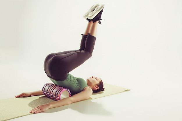 Vista frontal de una mujer joven que estira el cuerpo en la clase de gimnasia.