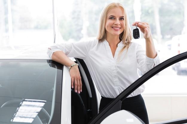 Vista frontal con una mujer joven que sostiene la llave del coche