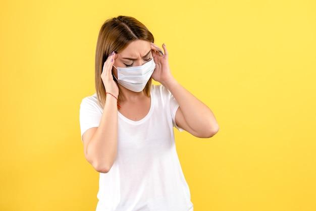 Vista frontal de la mujer joven que tiene dolor de cabeza en la pared amarilla