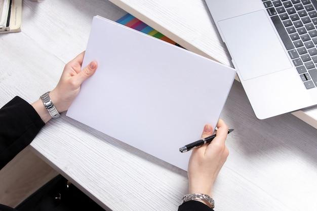 Una vista frontal mujer joven que trabaja con espacios en blanco vacíos delante de la mesa con ordenadores portátiles actividad empresarial