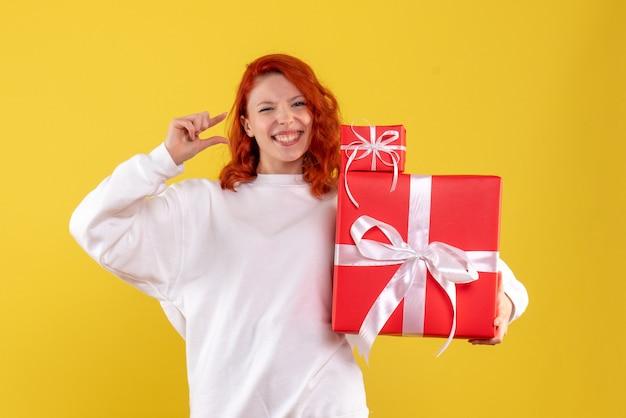 Vista frontal de la mujer joven con regalos de navidad en la pared amarilla