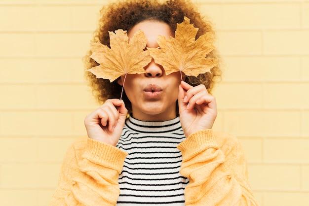 Vista frontal mujer joven rizada que cubre sus ojos con hojas