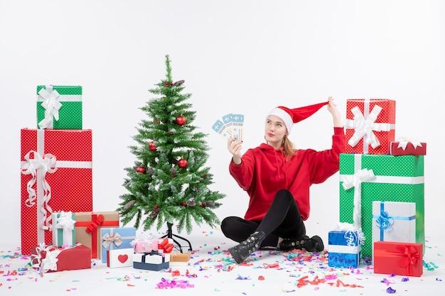Vista frontal de la mujer joven sentada alrededor de regalos sosteniendo boletos de avión en la pared blanca