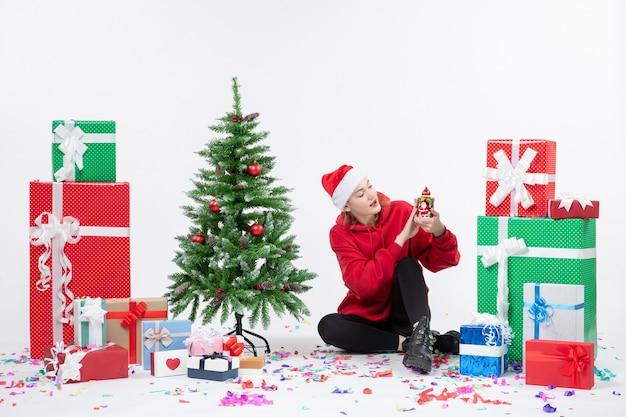 Vista frontal de la mujer joven sentada alrededor de regalos de vacaciones sosteniendo algo en la pared blanca