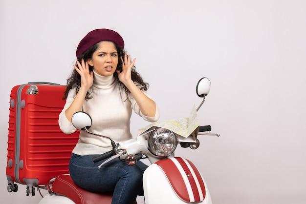 Vista frontal mujer joven sentada en bicicleta escuchando sobre fondo blanco color carretera motocicleta vehículo vacaciones mujer ciudad