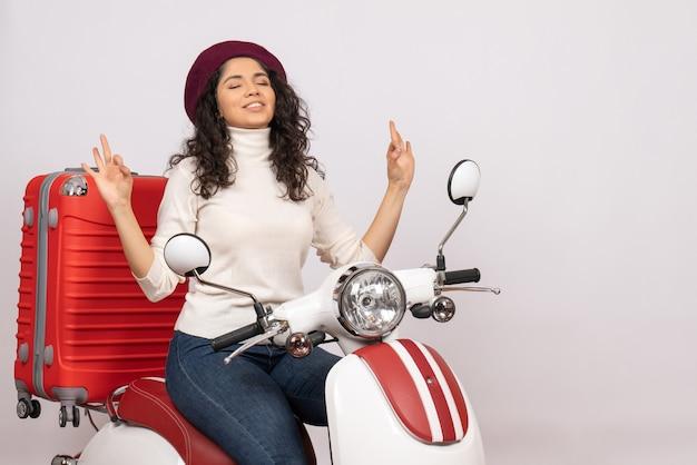 Vista frontal mujer joven sentada en bicicleta meditando sobre fondo blanco mujer vacaciones motocicleta ciudad color vehículo carretera