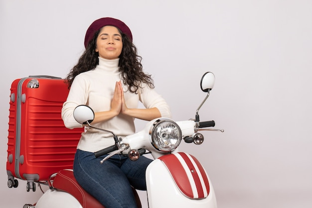 Vista frontal mujer joven sentada en bicicleta en pose de oración sobre fondo blanco mujer vacaciones motocicleta ciudad color vehículo carretera